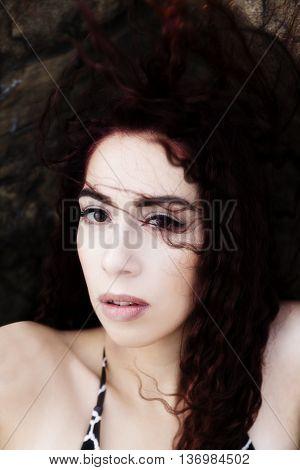 Hispanic Woman Outdoors Portrait Sitting On Rocks Wind Blowing Hair