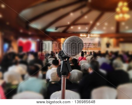 Microphone set up on blurred people in seminar event hall