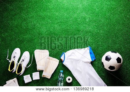 Soccer ball, cleats and various football stuff against artificial turf. Studio shot on green background. Copy space.