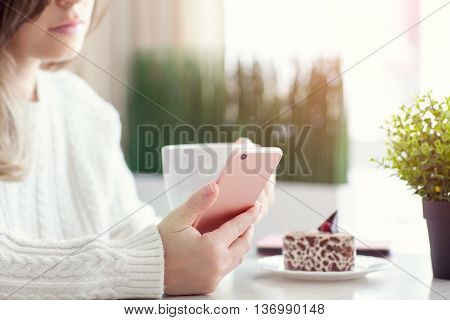 woman in cafe drinking caffee and holding pink phone