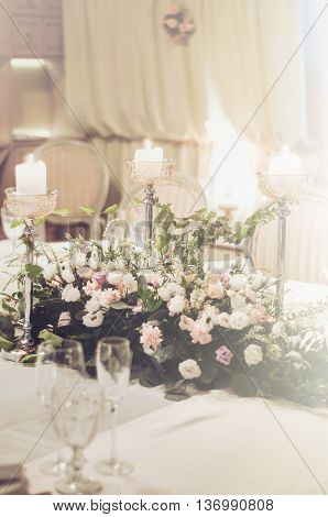 Wedding table setting with classic chairs elegant floristics decoration in banquet restoraunt. The floral composition of beige and pink roses flowers with high gold elegant candle coasters glass goblets for wine and champagne on white tablecloth. Selectiv