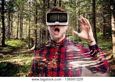 Hipster man in red checked shirt wearing virtual reality goggles. Mouth open in awe. Green forest.