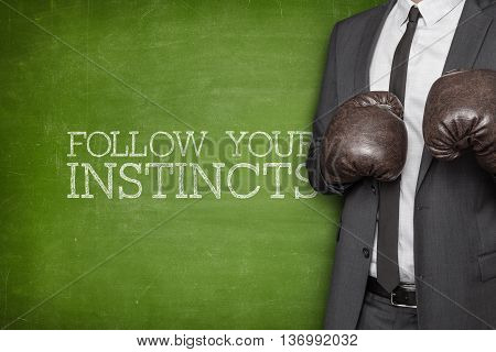 Follow your instincts on blackboard with businessman wearing boxing gloves
