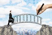 Success concept with hand drawing bridge over gap between two cliffs and businessman walking across it on city background with business sketches poster