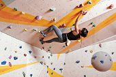 Young dexterous woman climber practicing in gym poster