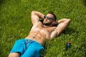 Handsome Muscular Shirtless Hunk Man Outdoor in City Park. Showing Healthy Muscle Body While Looking away, wearing sunglasses poster