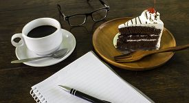A delicious cake with a coffee and the pocketbook.