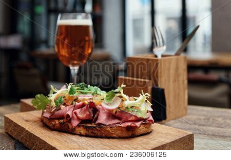 Sandwich with roast beef pastrami on restaurant table, toned image
