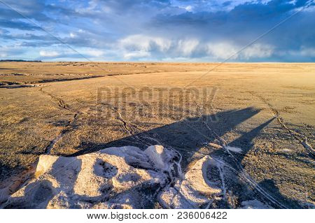 Rock formation with a long shadow and prairie in northern Colorado, early spring aerial view