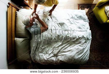 Elderly woman taking care of an elderly man