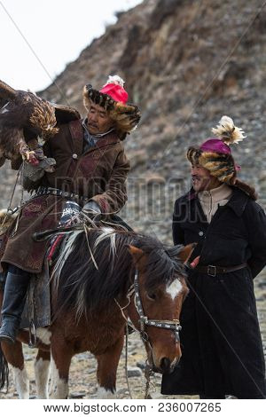 OLGIY, MONGOLIA - SEP 30, 2017: Kazakh Golden Eagle Hunter at traditional clothing, with a golden eagle on his arm during annual national competition with birds of prey Berkutchi of West Mongolia.