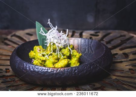 Food Sipped With Green Sauce Lies On A Dark Plate. The Dark Plate Is On The Table. Pasta From Transp