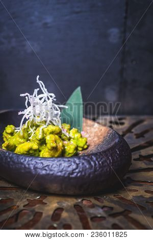 The Food Of Molecular Cuisine On An Iron Plate. Food Sipped With Green Sauce Lies On A Dark Plate. T