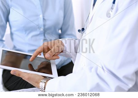Male Doctor Using Touchpad Or Tablet Computer While Consulting Female Patient In Hospital. Medicine