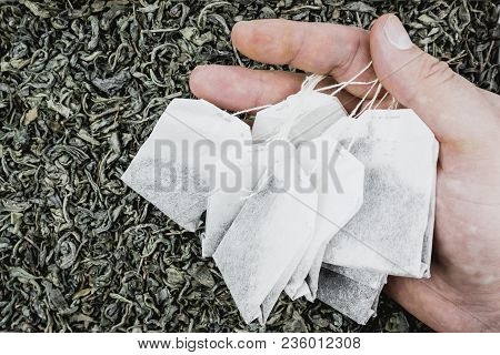 Paper Tea Bags In Hand On Dry Tea As Background