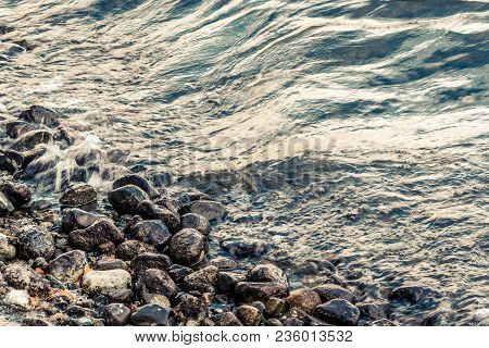 A Tidal Wave On The Beach With Grey Pebbles