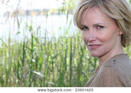 Head shot of woman by reeds on sunny day