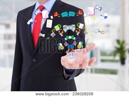 Businessman hand spread of with application icons coming up from it in the office ( blurred)