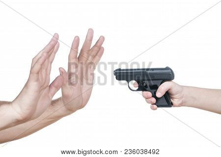 Child Hand With A Gun Aiming At The Male Hands Showing A Stop Isolated On A White Background