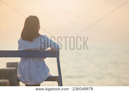 Lonely Woman Sitting On A Wooden Bridge Sunset.are Lonely.she So Sad