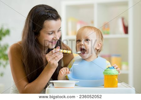 Mom Feeds Baby From Spoon. Little Boy Eats Healthy Food