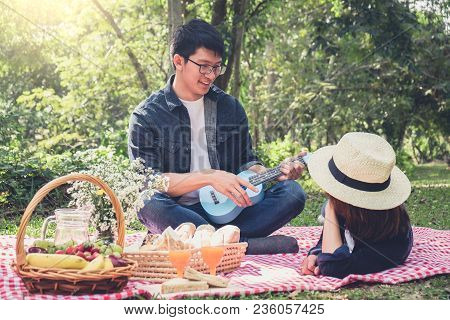 Happy Young Man Playing The Guitar Or Ukulele And Singing Song With Couple Love Sitting On Red Class