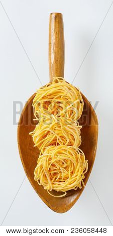 bundles of spaghetti pasta in wooden scoop