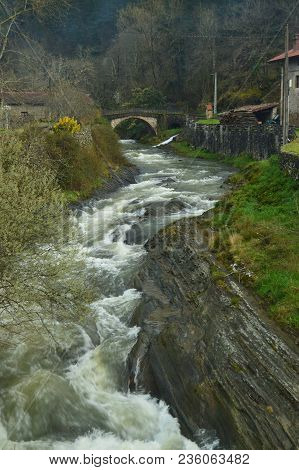 Beautiful Sinuous River With Brave Water And A Roman Bridge In The Background In The Gorbeia Natural
