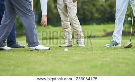 Team Of Golfers Standing And Talking In Golf Course While One Person Picking Up The Ball