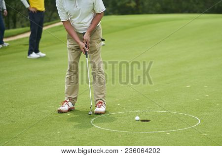 Unrecognizable Asian Man Putting Golf Ball On Green In Summer