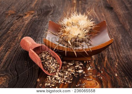 Silybum Marianum Flower And Seeds In Wooden Spoon On Wooden Table.