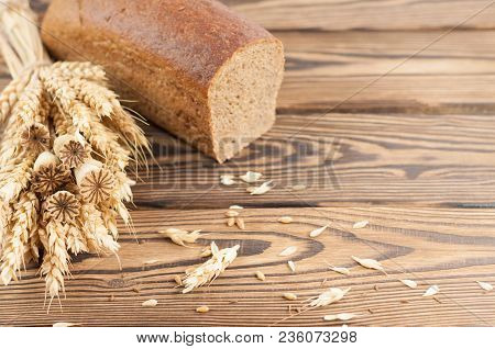 One Bundle Of Wheat And Poppy And Lot Of Scattered Grain And Half Of Bread On Old Rustic Wooden Plan