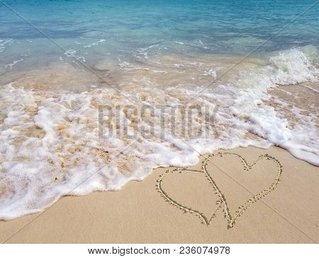 Pair Of Hearts In Beach Sand With Frothy Ocean Surf And Turquoise Ocean Water