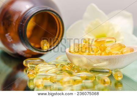 Fish Oil Capsule And Wooden Spoon Light Background Health Care And Medical Concept. Wooden Spoon Of