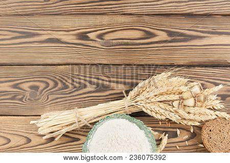 One Bundle Of Wheat And Poppy And Lot Of Scattered Grain And Slice Of Bread And Flour In Glass Bowl