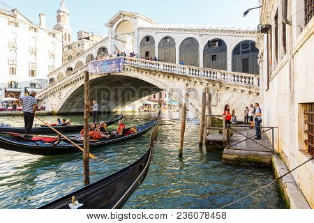 Venice, Italy - June, 21, 2013: View Of Gondolas With Passenges And Ponte Di Rialto, Many Tourists O
