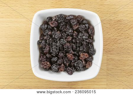 Overhead Shot Of Raw Zante Currants, In A White Bowl On A Wooden Chopping Board Background. Zante Cu