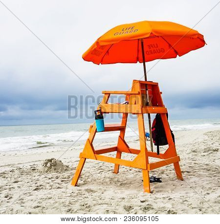 An Orange Lifeguard Stand And Umbrella On The Beach