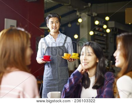 Young Asian Waiter Serving Female Customers In Coffee Shop, Shot Through Window Glass.