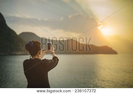 Woman Taking Sun Rise Photograph By Smart Phone At Sea Side