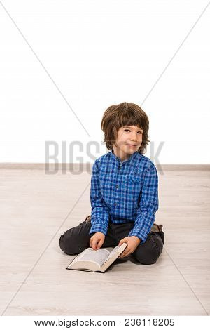 Smiling Little Cute Boy Sitting On Floor And Reading Book