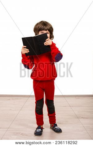 Smiling Boy Holding And Looking Over The Book Against White Background