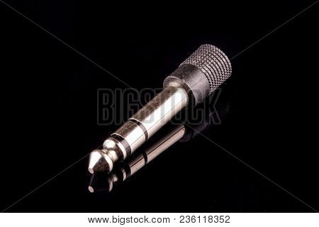 Silver Plated 3.5 Mm Audio Jack Against Black Background
