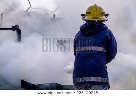 Fire Fighter Use Co2 (carbon Dioxide) Fire Extinguisher To Extinguish A Fire Create White Smoke And