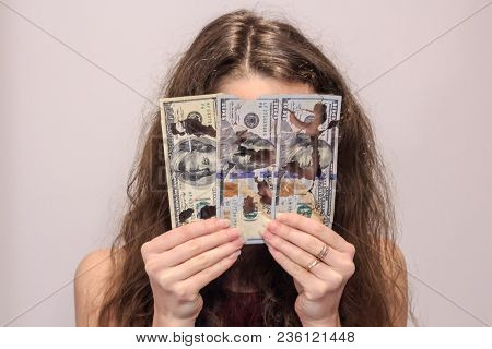Close-up Portrait Of Young Woman Looking Through The Spoiled Dollar Bills