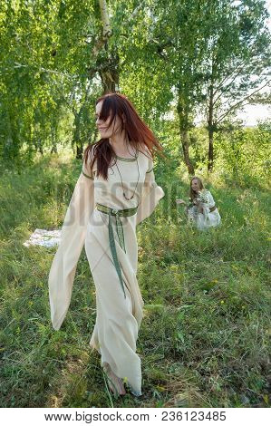 Two Attractive Women In Traditional Russian Clothes Relaxes Over Nature Background. Ivan Kupala Holi