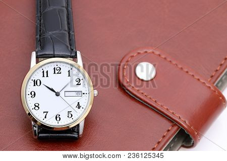 Wrist Watch With Leather Strap On Business Notebook