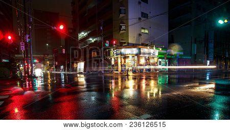 Osaka, Japan - April 14, 2018: Car Lights On A Quiet Street In Heavy Rain