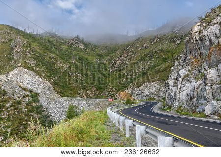 Winding Asphalt Road Through The Pass, Part Of A Mountain Serpentine, Rocks, Trees And Fog On The Ba