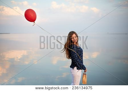 Portrait Of Young Woman With Red Air Balloon And Present Bag Near The Calm Sea Or Lake. Clouds Are R